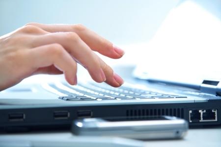 tecla enter: Las manos humanas de trabajo en la computadora port?til en el fondo de oficinas Foto de archivo
