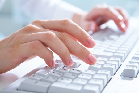 Femme mains tapant sur le clavier d'ordinateur blanc