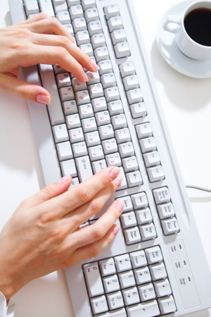 keyboard key: Female hands typing on white computer keyboard on white desk