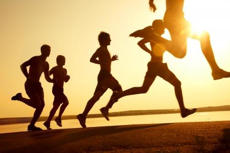 фитнес: Группа молодых людей работает на пляже на красивый закат лета