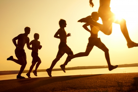 uomo rosso: gruppo di giovani corre in spiaggia sul tramonto bella estate