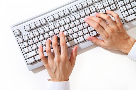 Femme mains tapant sur le clavier d'ordinateur blanc sur le bureau blanc