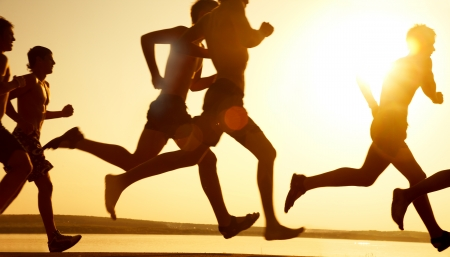 jogging in nature: group of young people runs at the beach on beautiful summer sunset Stock Photo