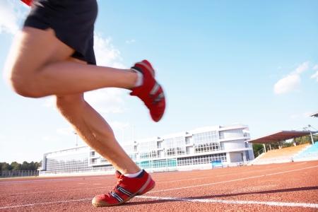 legs of sportsman running on stadium photo