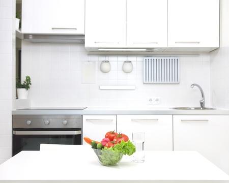 intérieur de la petite cuisine blanche avec des légumes frais sur la table Banque d'images