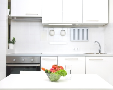 interior of small white kitchen with fresh vegetables on the table photo