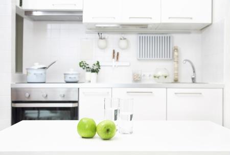 intérieur de la petite cuisine blanche avec des pommes fraîches sur la table