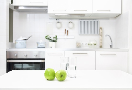 domestic kitchen: interior of small white kitchen with fresh apples on the table