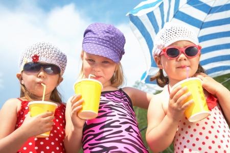 Trois petites filles mignonnes boire sur la plage