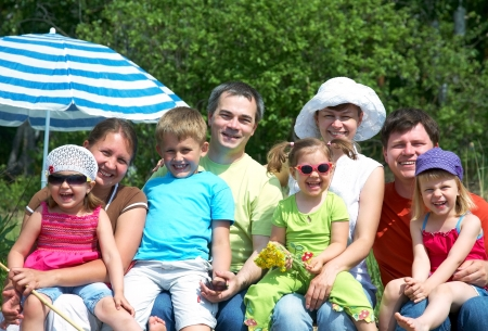 Portrait of big family  with their little daughter under beach umbrella  photo