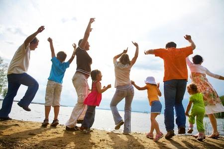 家庭: 大家族的成人和兒童在沙灘上跳舞