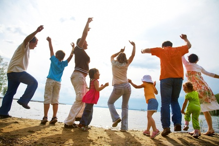 fun woman: Big family from  adults and children dancing on the beach