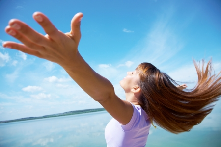 outdoor living: beautiful young woman opened her hands with delight at the blue sky Stock Photo