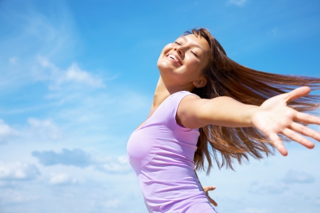excite: beautiful young woman opened her hands with delight at the blue sky Stock Photo