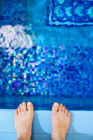 edges: View of bare male feet at swimming pool side