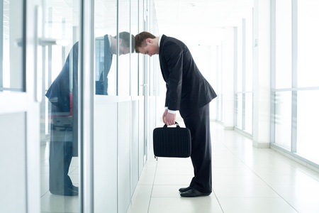 discord: young business man leaned against glass wall in crisis moment