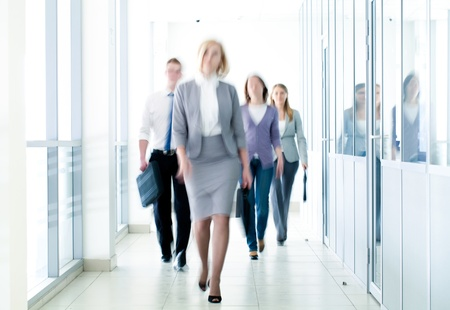 women business: businesspeople walking in the corridor of an business center, pronounced motion blur