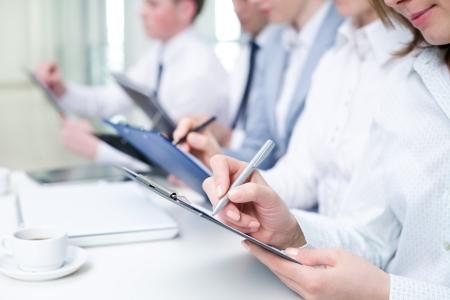 Close-up van business mensen handen schrijven op papier