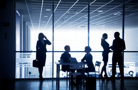 Several silhouettes of businesspeople interacting  background business centre Stock Photo - 21894593