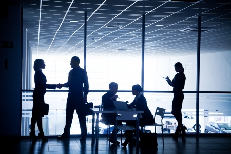 Several silhouettes of businesspeople interacting  background business centre Stock Photo - 21894595