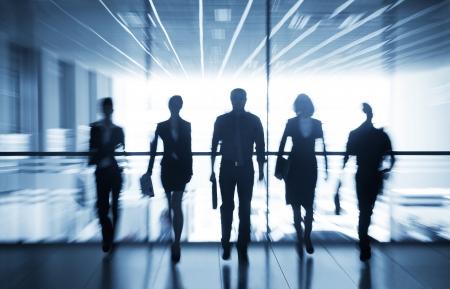 Plusieurs silhouettes de gens d'affaires interagir fond de bureau