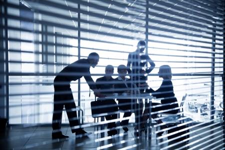 Plusieurs silhouettes de gens d'affaires interagir centre d'affaires de fond