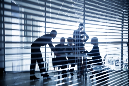 business transaction: Several silhouettes of businesspeople interacting  background business centre