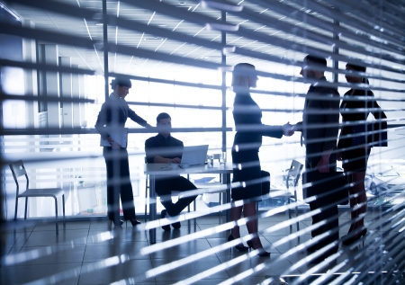 Several silhouettes of businesspeople interacting  background business centre Stock Photo - 21894601