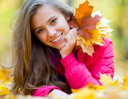 lying in leaves: Horizontal image of a cheerful girl lying in autumn leaves Stock Photo