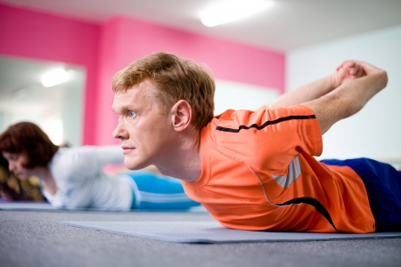 Portrait of young man doing yoga with other people in background