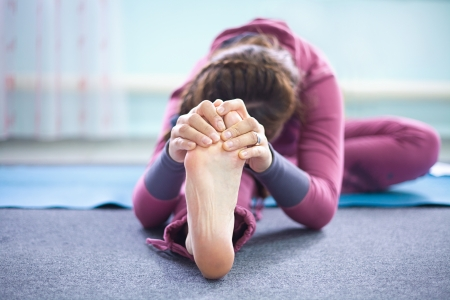 Woman practicing yoga at health club