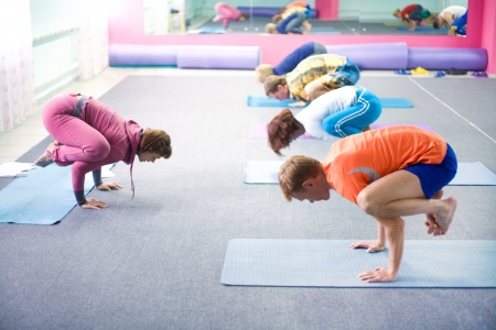 people practicing yoga at health club