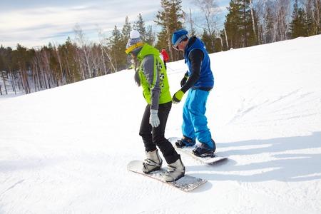 Couple de jeunes snowboarders dans une station de ski