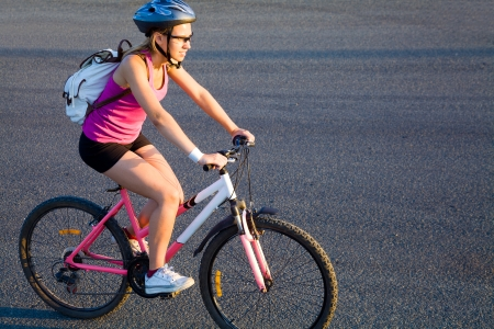 young sporty woman in helmet cycling outdoor