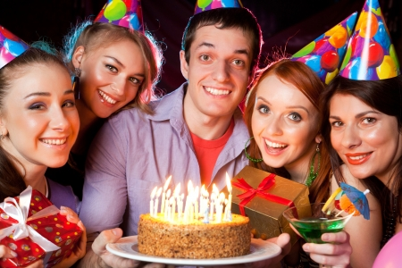 cheerful young company celebrates birthday in a nightclub