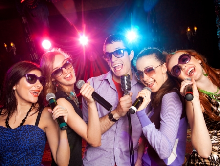 group of young people singing into  microphone at  party. karaoke photo