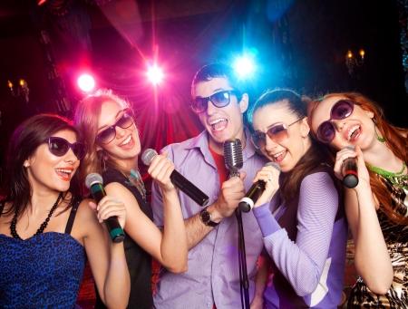 groupe de jeunes gens qui chantent dans le microphone à la fête. karaoke