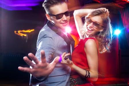 noche: pareja de jóvenes se divierten bailando en la fiesta. Foto de archivo