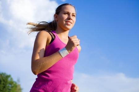 Jeune fille sportive s'exécute sur un fond de ciel bleu