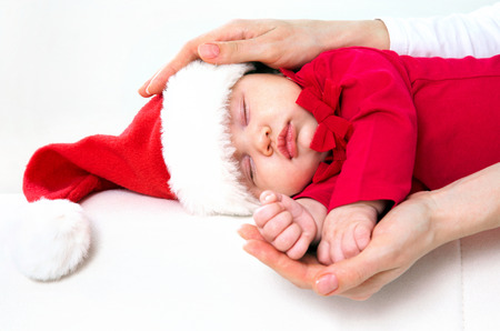 Cute baby in Santa hat sleeping in mother's hands