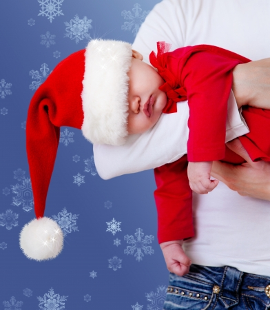 Portrait of Christmas baby is sleeping on mother's hands photo