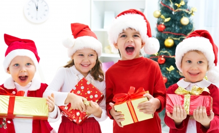 xmas baby: Group of four children in Christmas hat with presents Stock Photo