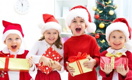 Groupe de quatre enfants en chapeau de Noël avec des cadeaux