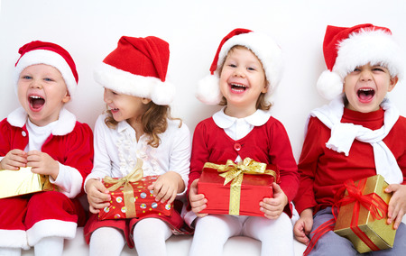 friends party: Group of four children in Christmas hat with presents Stock Photo