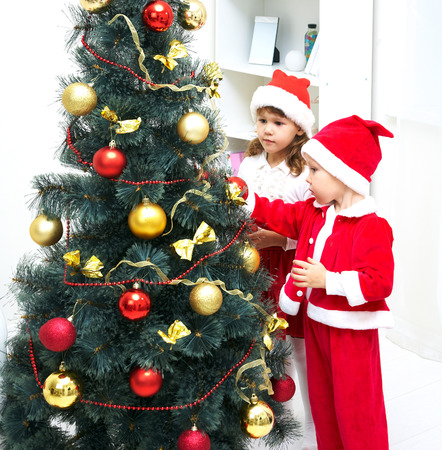 Cute little boy and girl decorating Christmas tree photo