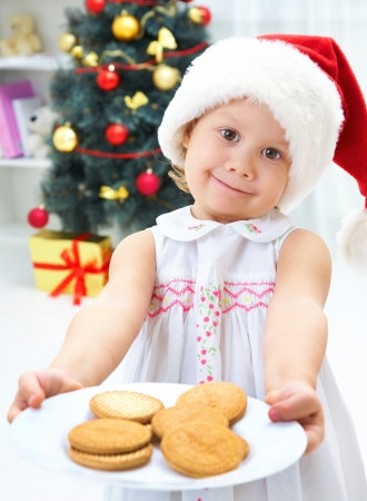 Cute girl in Santa hat standing a treat Christmas biscuits photo