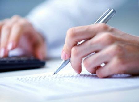 Photo of hands holding pen under document  and pressing calculator buttons Standard-Bild