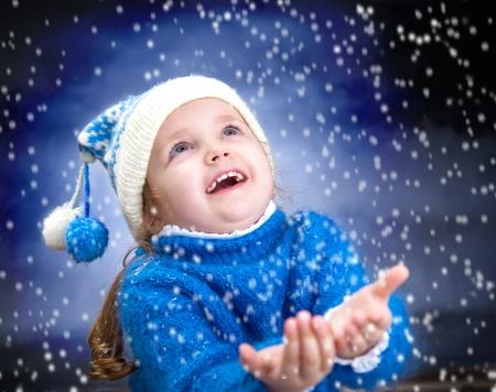 Portrait d'une petite fille de l'hiver avec des flocons de neige