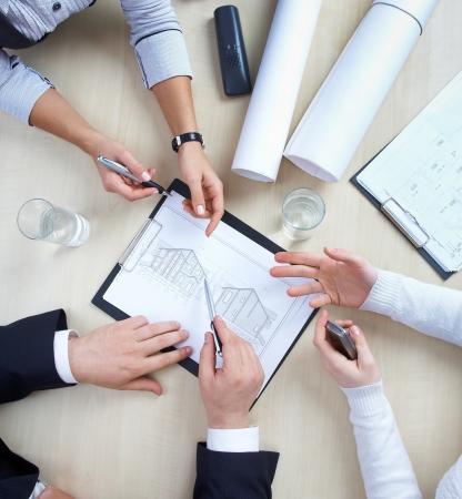 Trois collègues discutent d'un projet de maison ronde de table