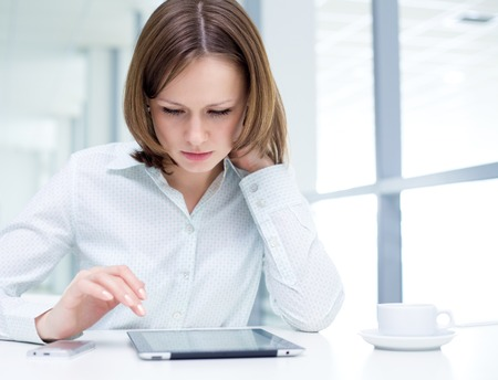 manos trabajo: Mujer joven que usa una tableta digital Foto de archivo